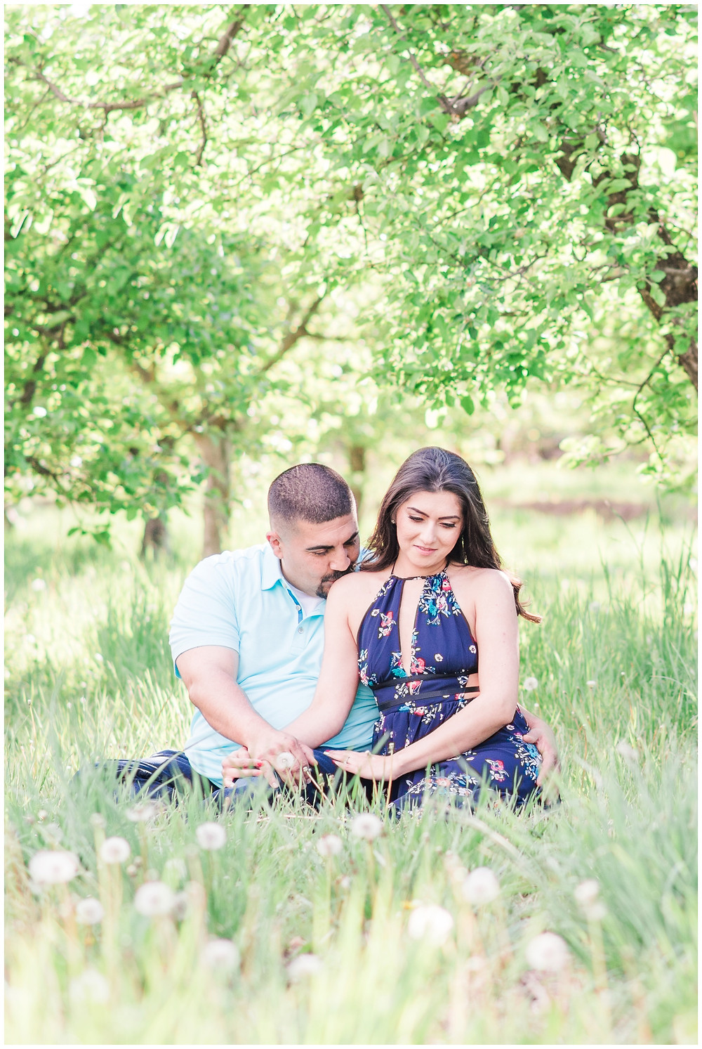 Flower tree engagement in corrales, new Mexico. Albuquerque wedding photographer Maura Jane Photography. Couple in blue outfits sitting in grass field