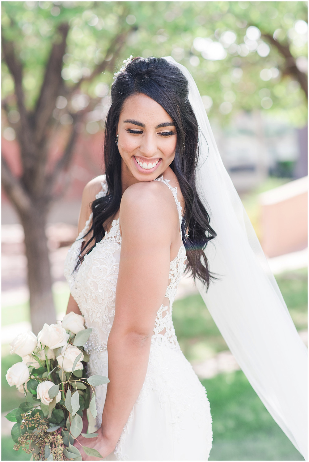 Bride before ceremony with wedding veil and white rose bouquet in white lace wedding dress