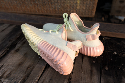 A pair of Adidas Yeezy Boost 350 V2 Butter with a rubber faded sole from butter yellow to a salmon pink. The collar, heel tab, and rubber dripped laces were also added in salmon pink. The rubber material is individually mixed for each color and shoe. Rubber Dripped Yeezys