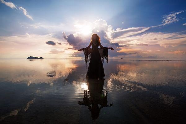 Elegant woman walking on water. Sunset a