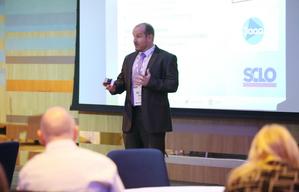 Steve O'Hare delivers a presentation to a room of delegates