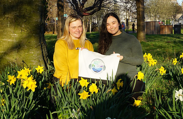 Two women surrounded by daffodils. The women hold a WAC podcast tote bag. The women on the left is blonde and wears a yellow shirt and the women on the right is brunnette and wears a green shirt