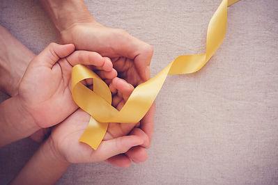 hands-holding-yellow-gold-ribbon-sarcoma