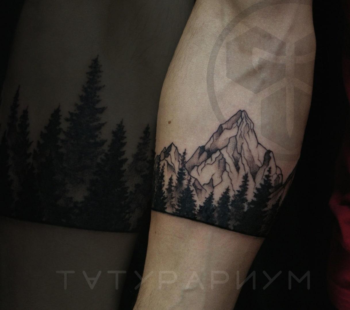 Фото татуировки, лес и горы вокруг руки,