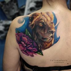 Лев и цветок на спине у девушкив реализм