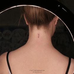надпись у девушке на тыльной стороне шеи