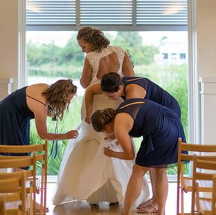 bridesmaids helping bride dress bustle