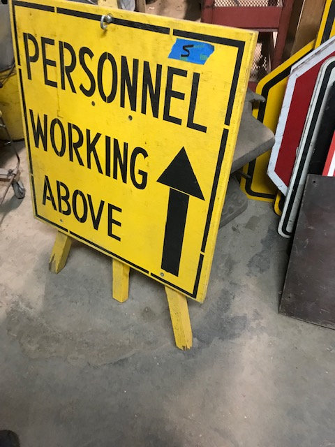 Personnel Working Above Street Sign