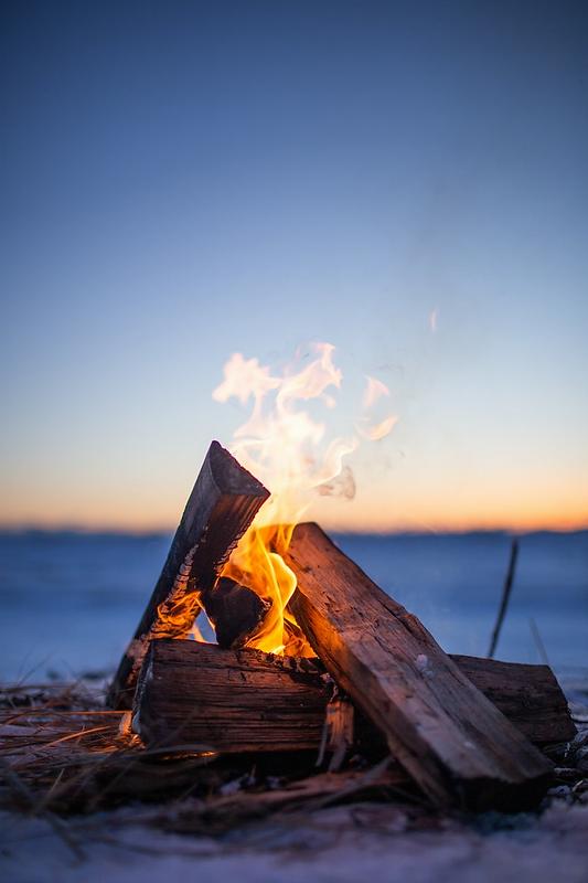 Lagerfeuer in der Dämmerung an einem See