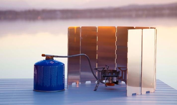 Campingkocher mit Gas auf Campingtisch mit Winschutz