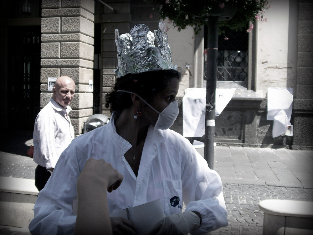 a woman wearing a lab coat, a lab mask and a crown of silver cocks. otherwise a normal sunny day in Italy