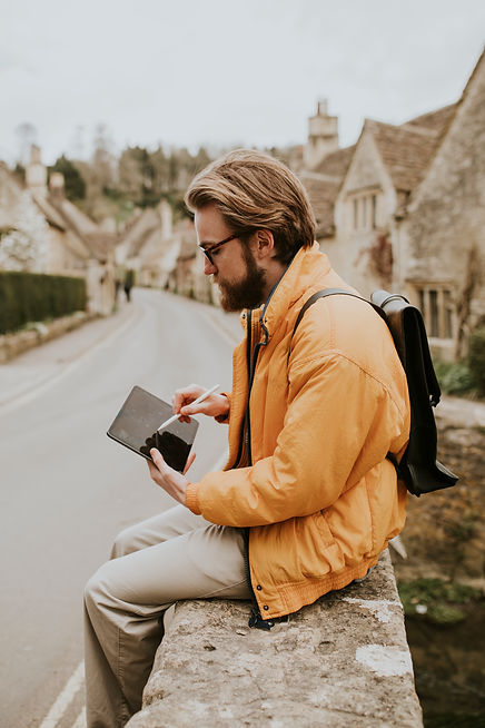 man-taking-notes-his-tablet-cotswolds-village-uk.jpg