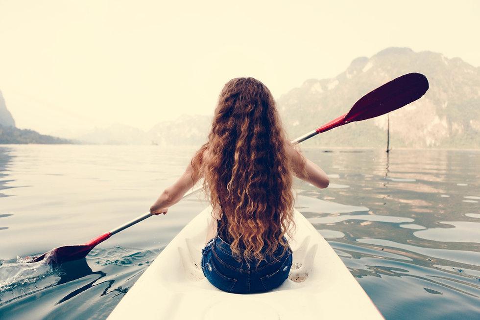 Woman paddling a canoe through a nationa