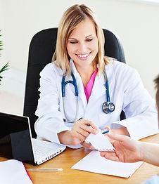 Female doctor at desk handing over paper note