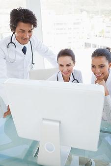 Team of doctors looking at computer screen