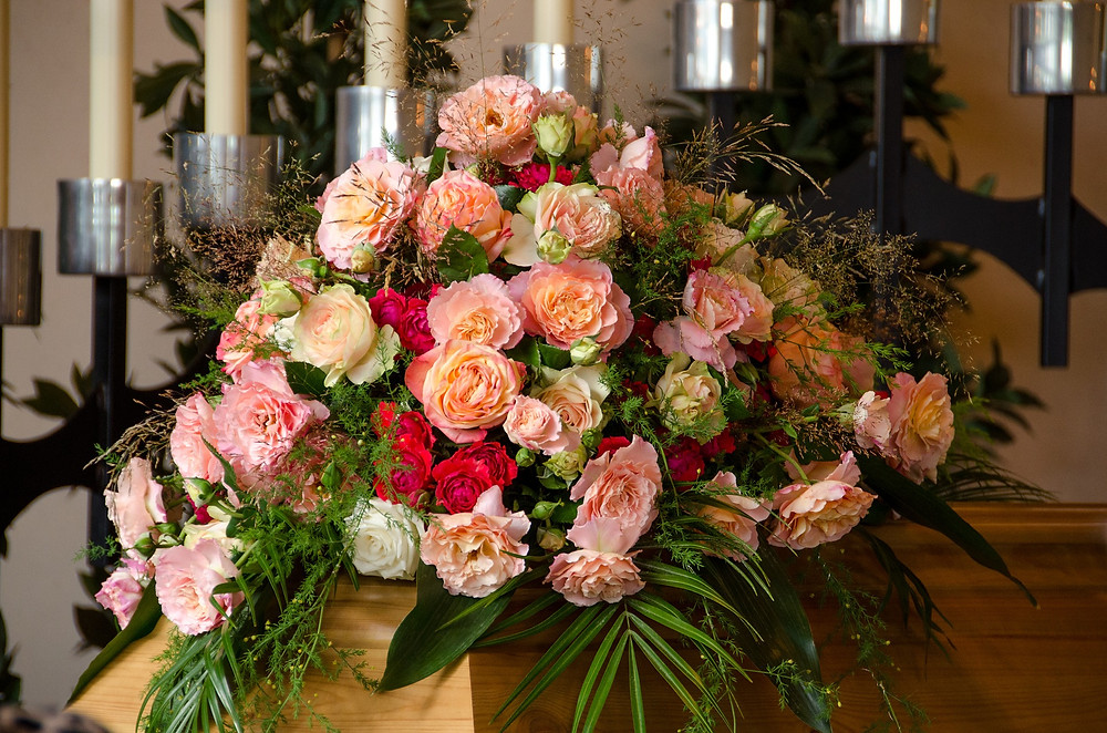 This tastefully colourful casket spray is not only a tribute to a lost loved one, but a reminder of the many joyous times spent together. The beautiful bouquet includes peach roses, light pink spray roses, coral spray roses, cerise roses,  and assorted greenery.​