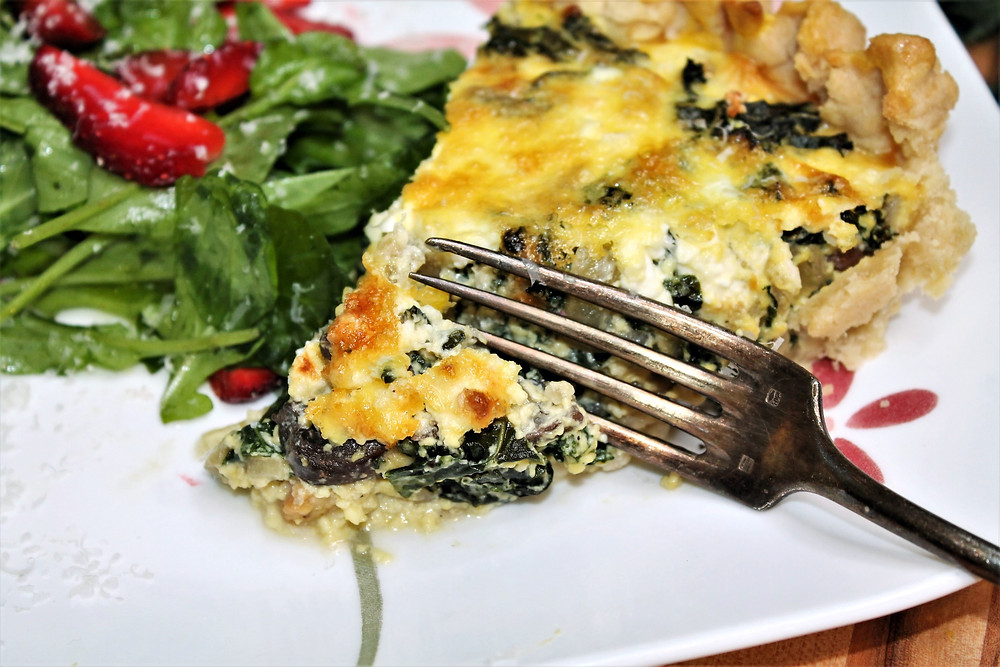 slice of quiche on white plate with fork and side salad