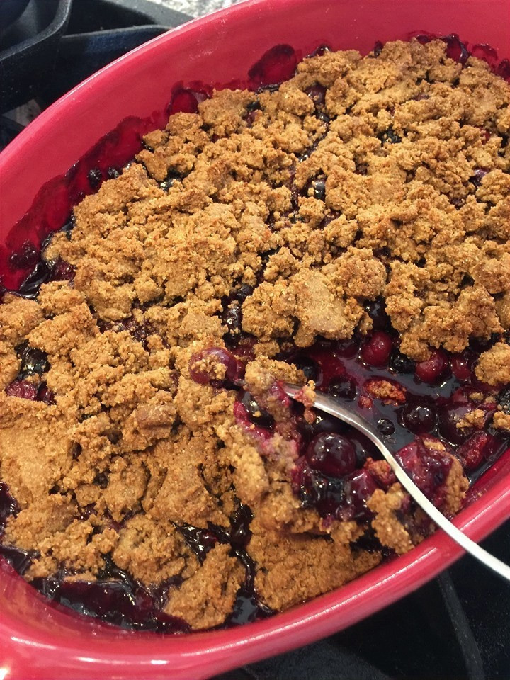Homemade blueberry cobbler with grammar cracker crust in a bright red baking dish