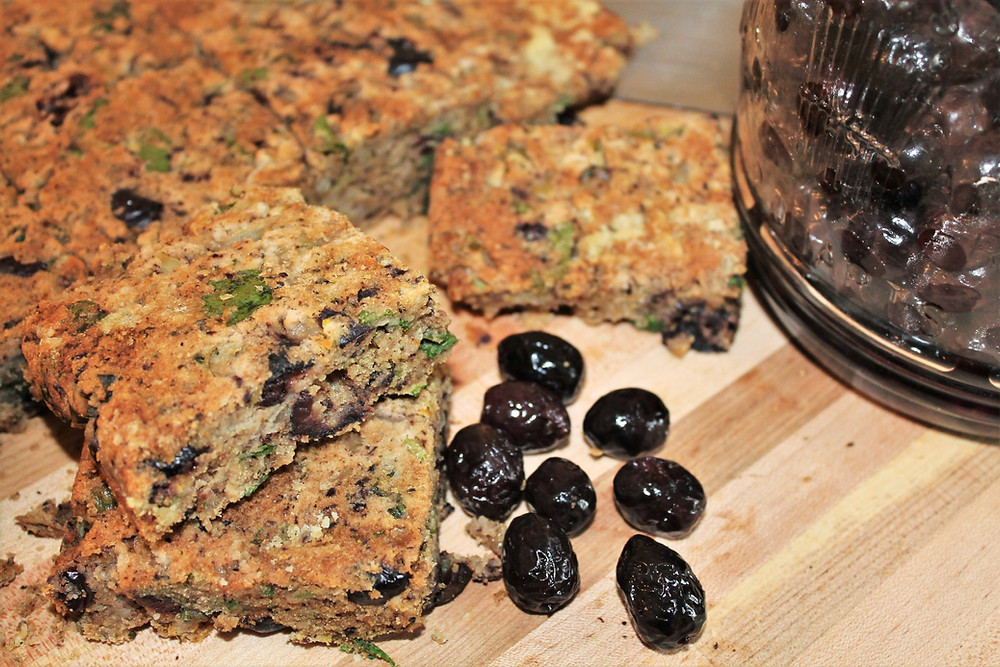 black olives on wooden cutting board and olive bread