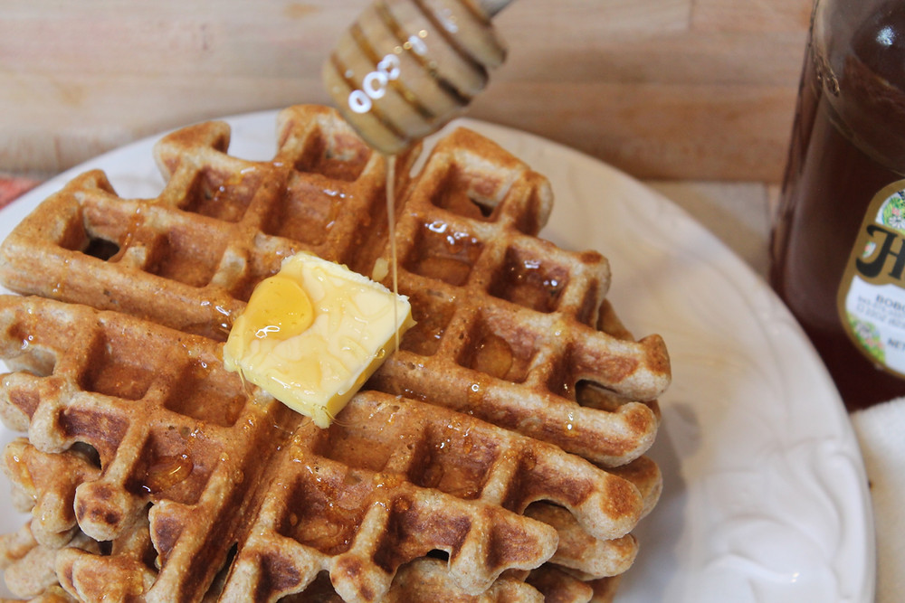 pouring honey over waffles