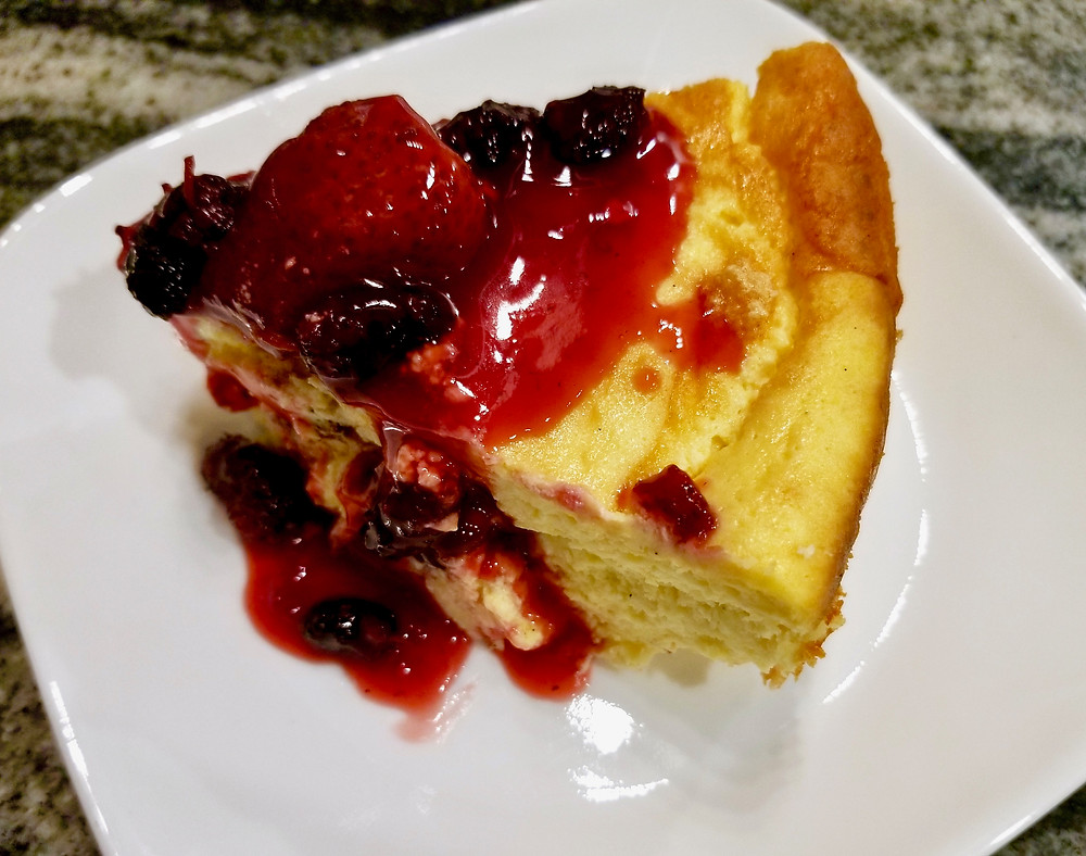 Slice of baked farmer's cheese topped with berries