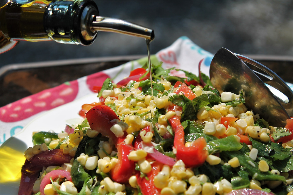 drizzling olive oil over the salad