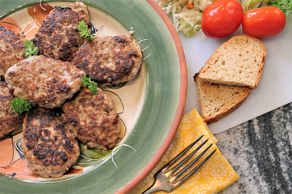 meatballs cooked on a platter with bread, pickled tomatoes