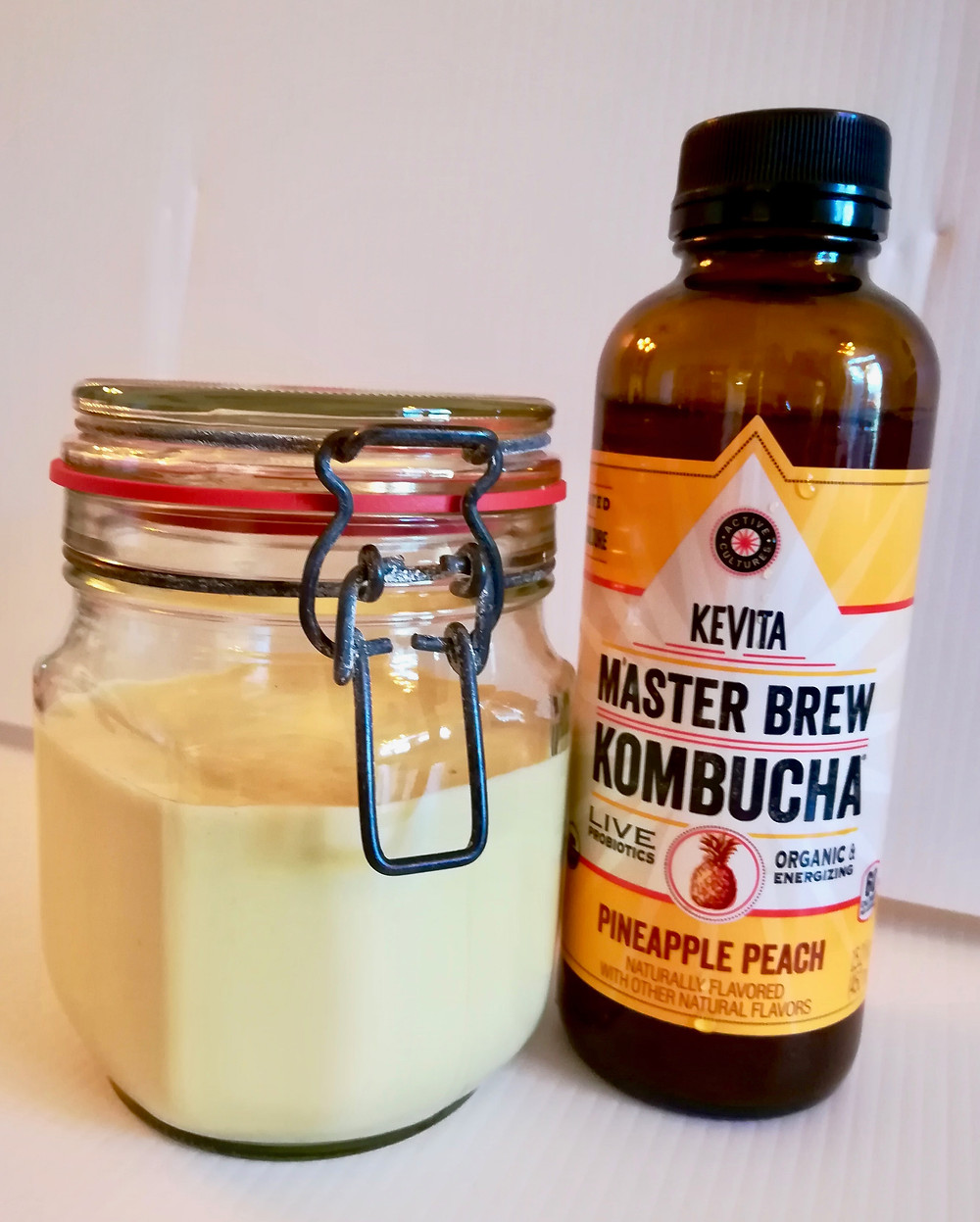 Jar of homemade kombucha mayonnaise with a bottle of kombucha