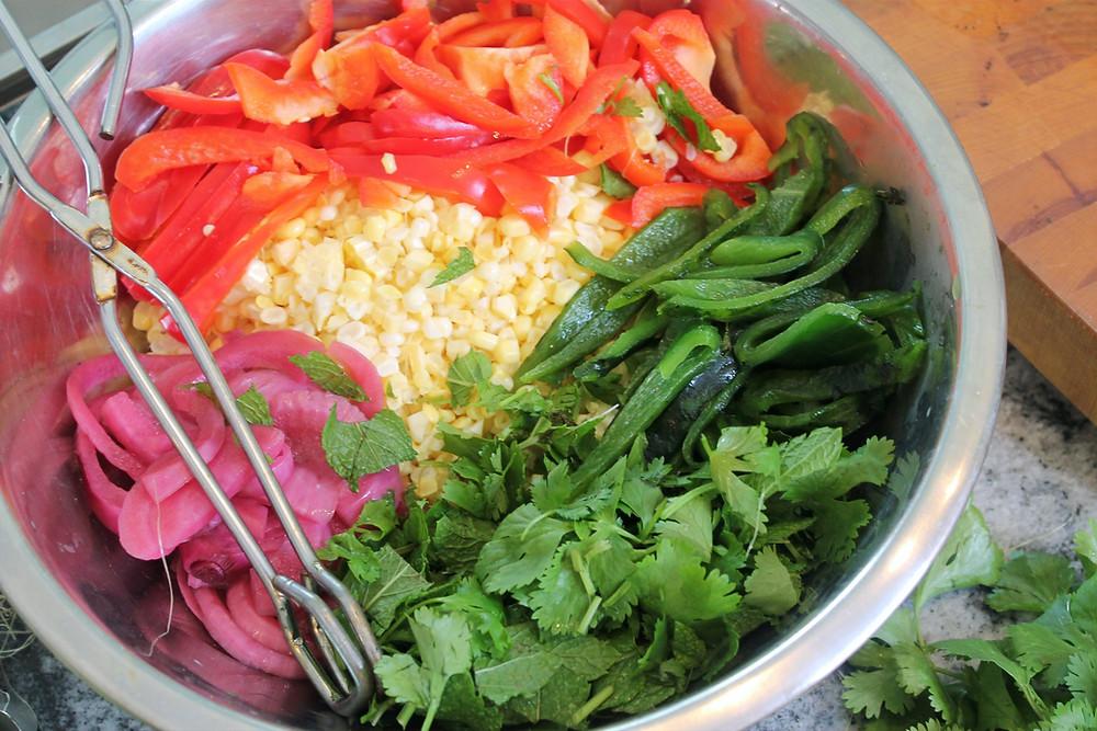 bowl of corn shredded, red pepper stripes, poblano pepper, herbs