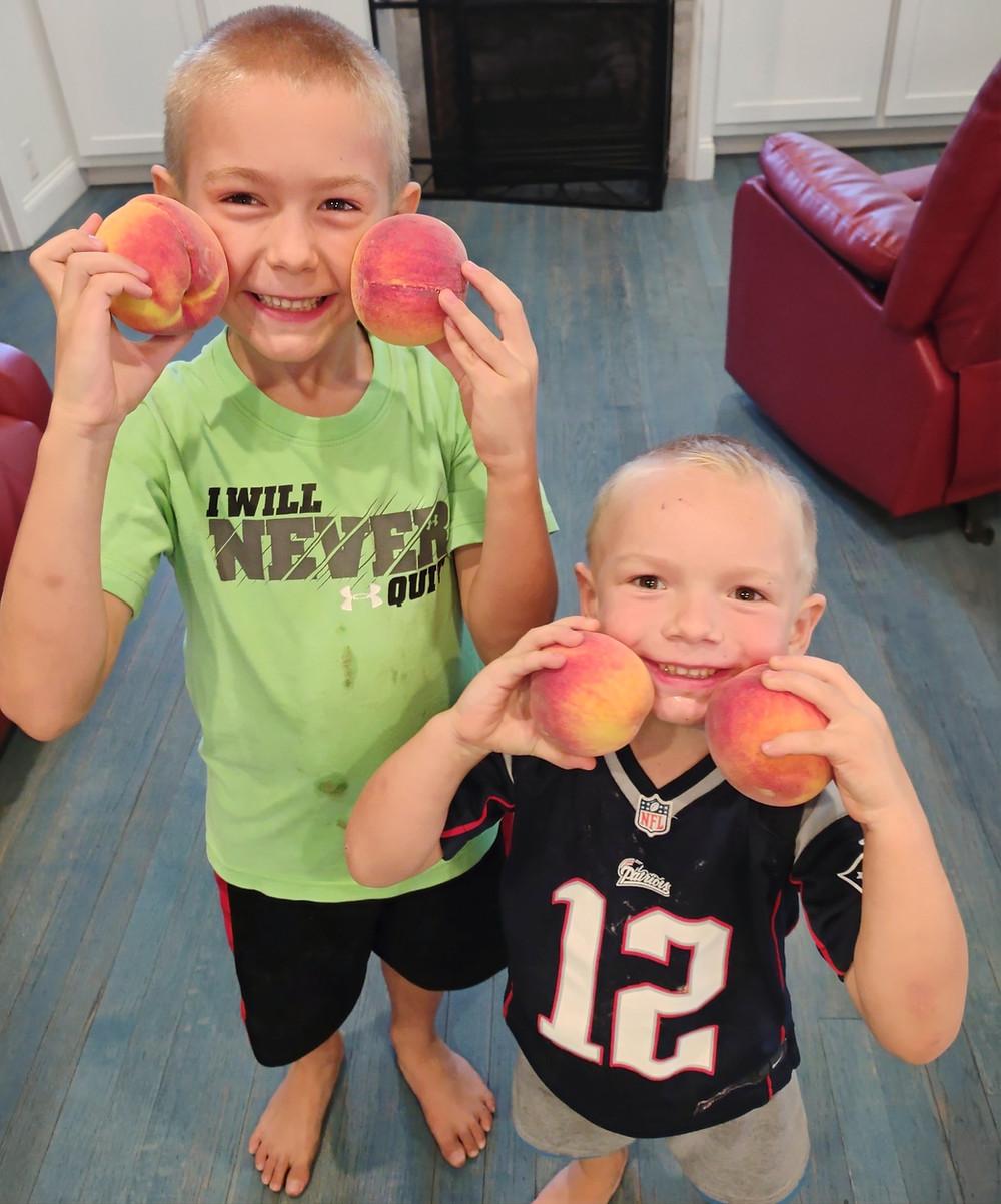two boys holding peaches