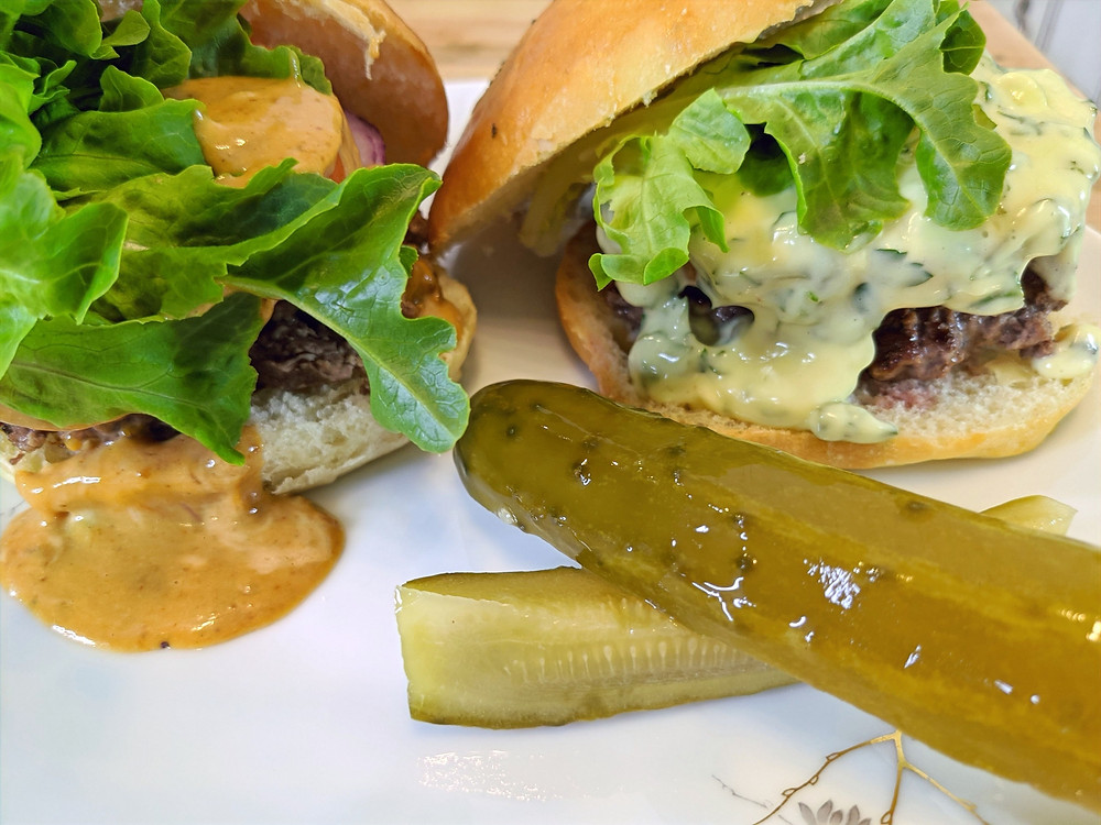Two hamburgers with homemade buns topped with lettuce and aioli sauce with pickles on the side