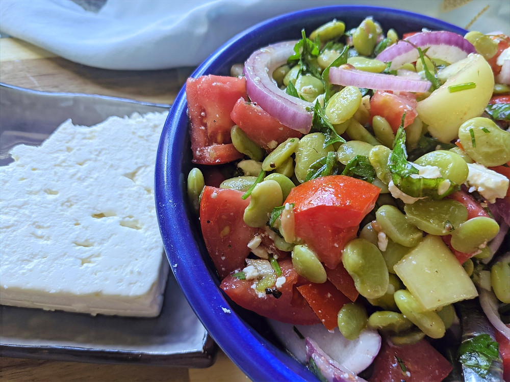 Bowl full of salad made with butter beans, tomatoes, onions, and herbs, with a block of feta cheese on the side