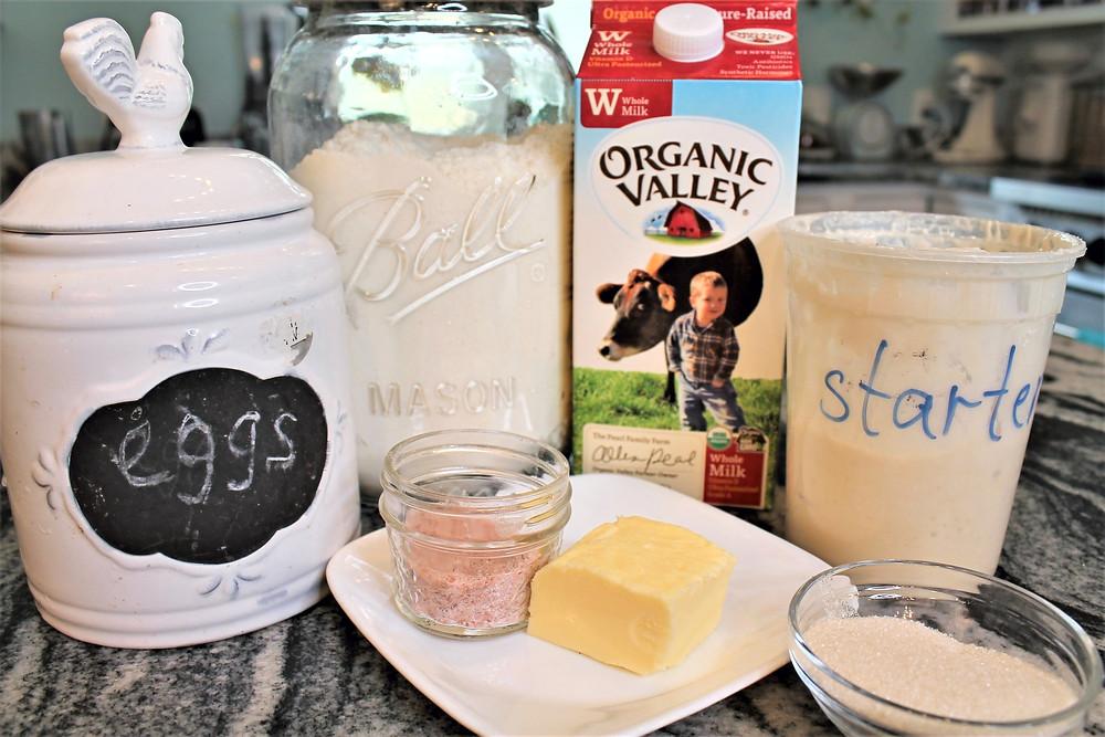 eggs, flour in a glass jar, milk, starter, salt, butter