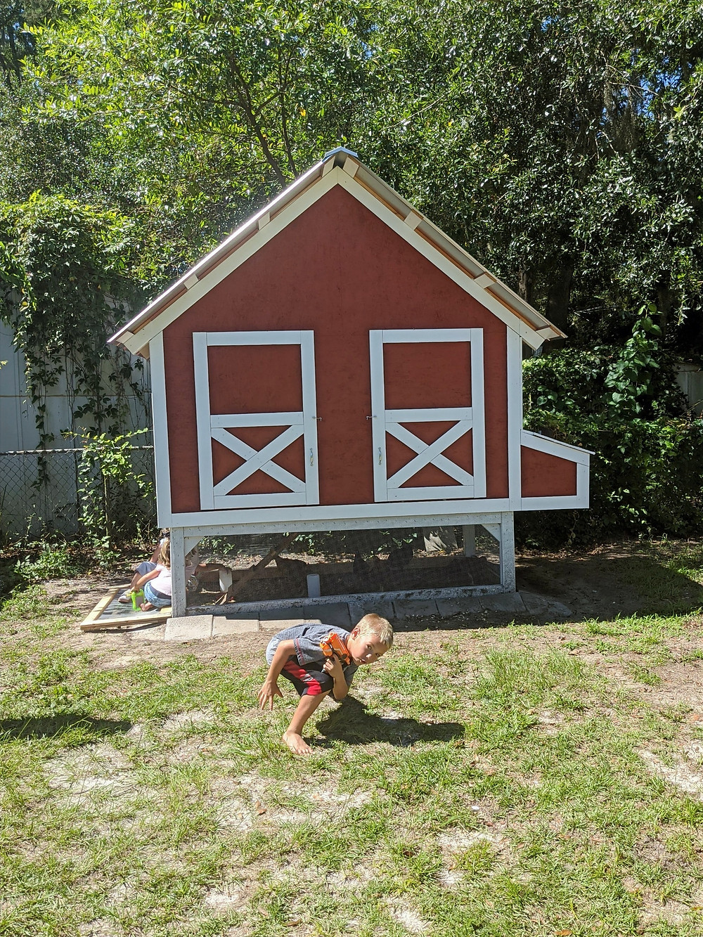 Young boy ducking in front of red chicken coop