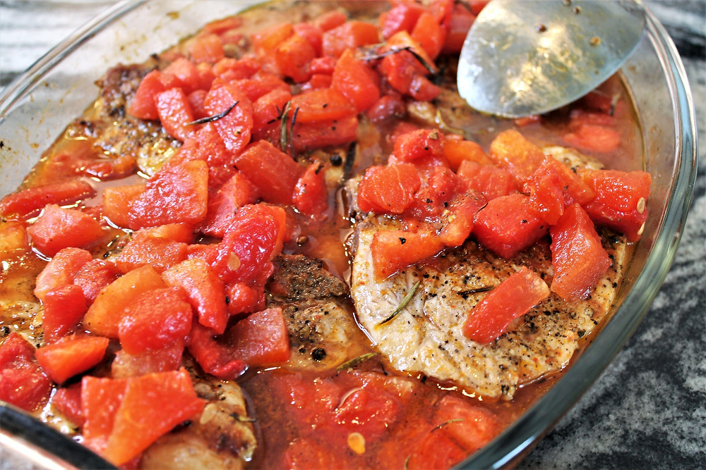 pork chops with braised watermelon on top in casserole dish with a spoon