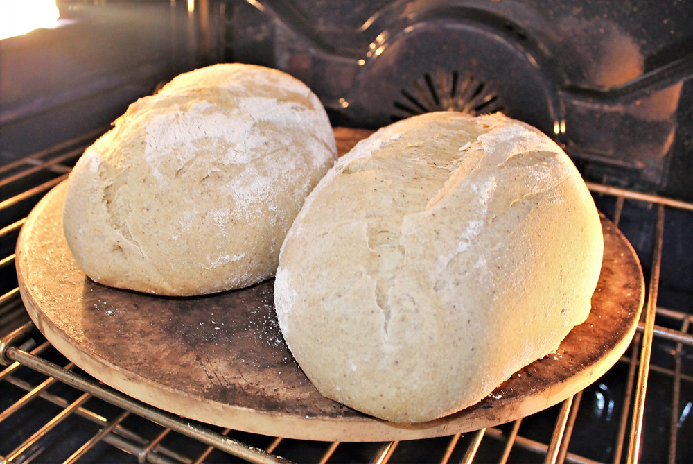 two loaves of bread on a pizza stone in the oven