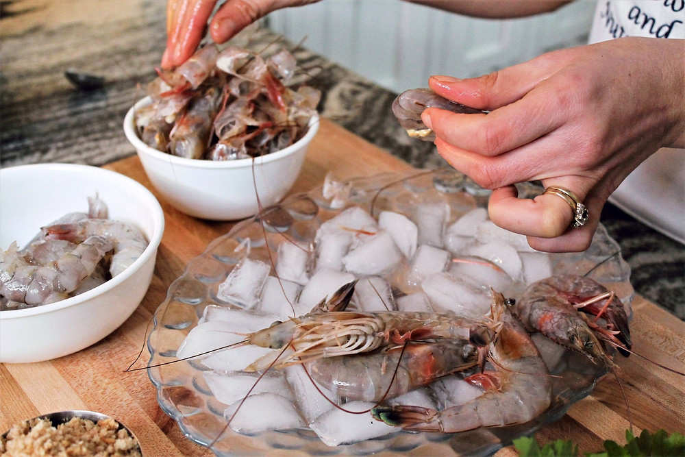shrimp on an ice and two white bowls with shrimp heads and cleaned shrimp