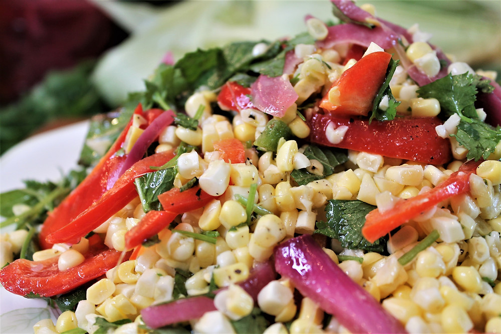 corn salad with red peppers, red onions, herbs
