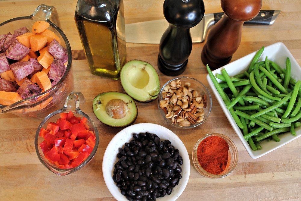 sweet potato cubes, black beans, green beans, avocado, olive oil, nuts, sweet red pepper, knife, black pepper, salt, paprika