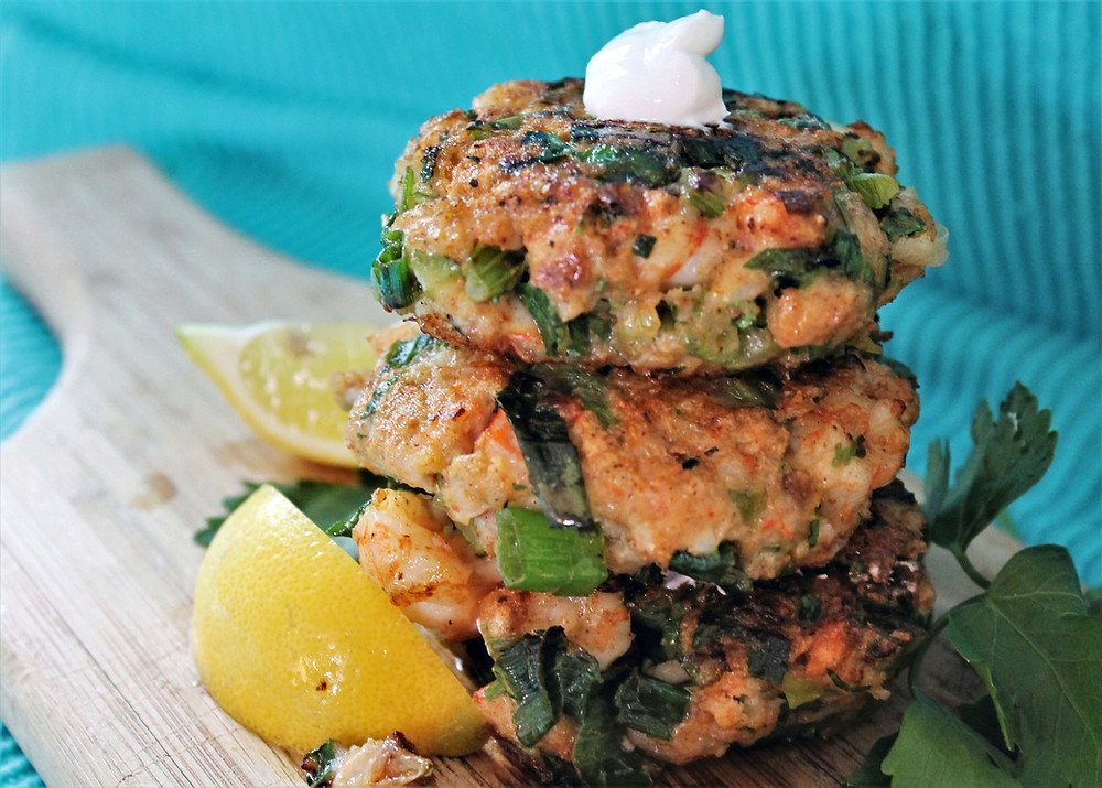 shrimp cakes on a wooden board and slices of lemon