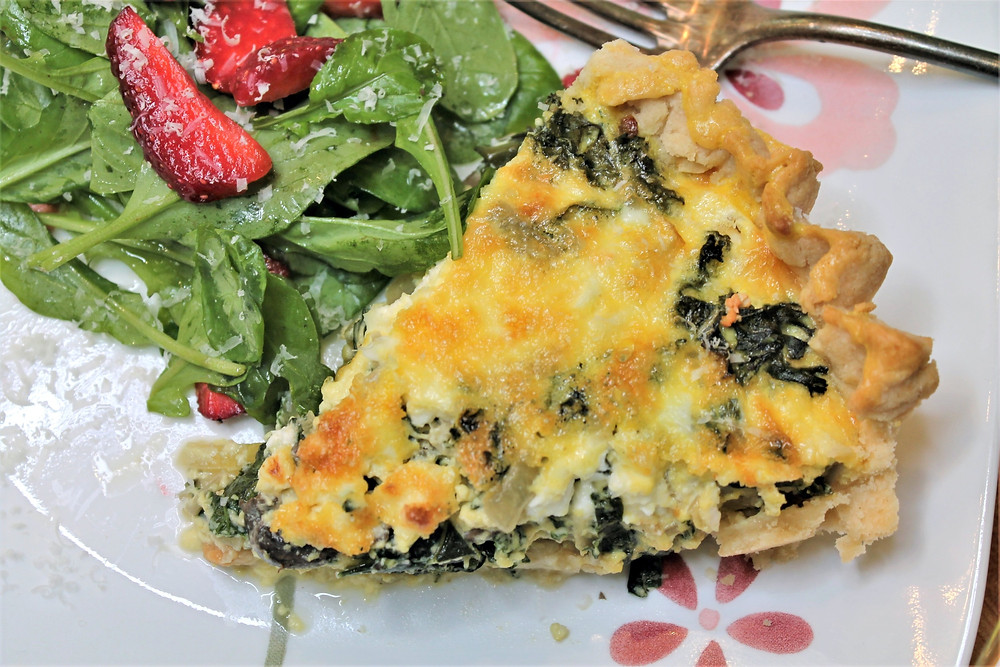 quiche on a plate with side salad