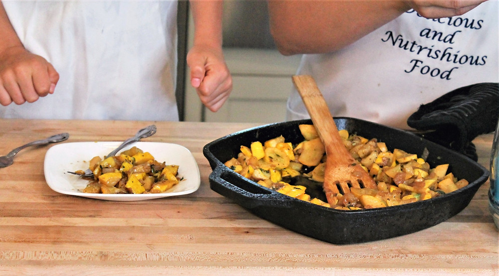 cooked summer squash on a white plate and on a skillet