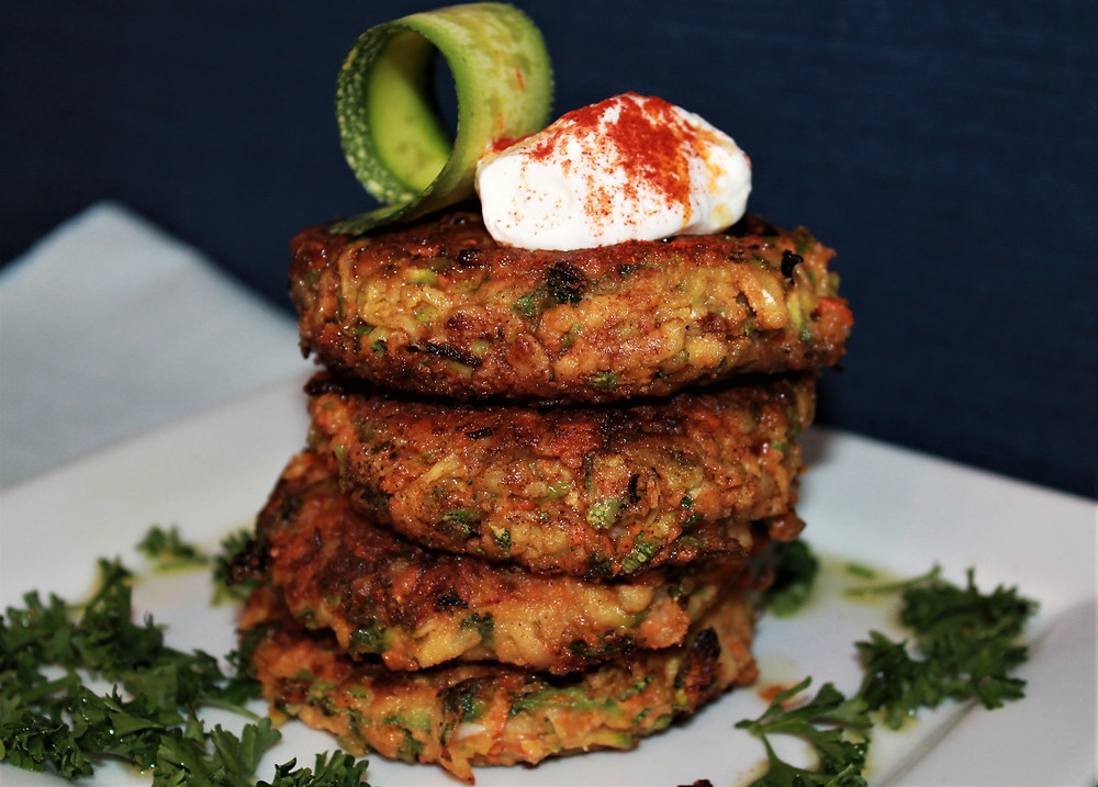 Stack of homemade cheesy zucchini fritters topped with a slice of zucchini and white cream