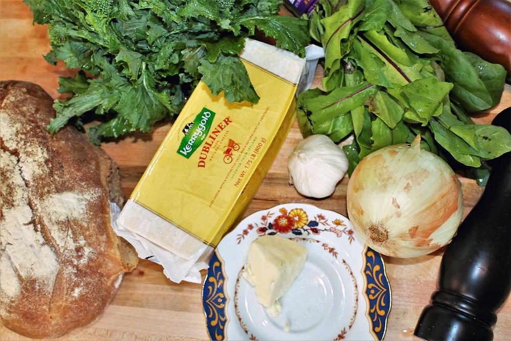 bread, greens, cheese, butter, onion, garlic on wooden board