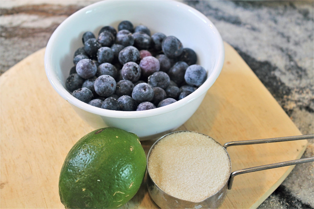 blueberries in a white bowl, lime, sugar