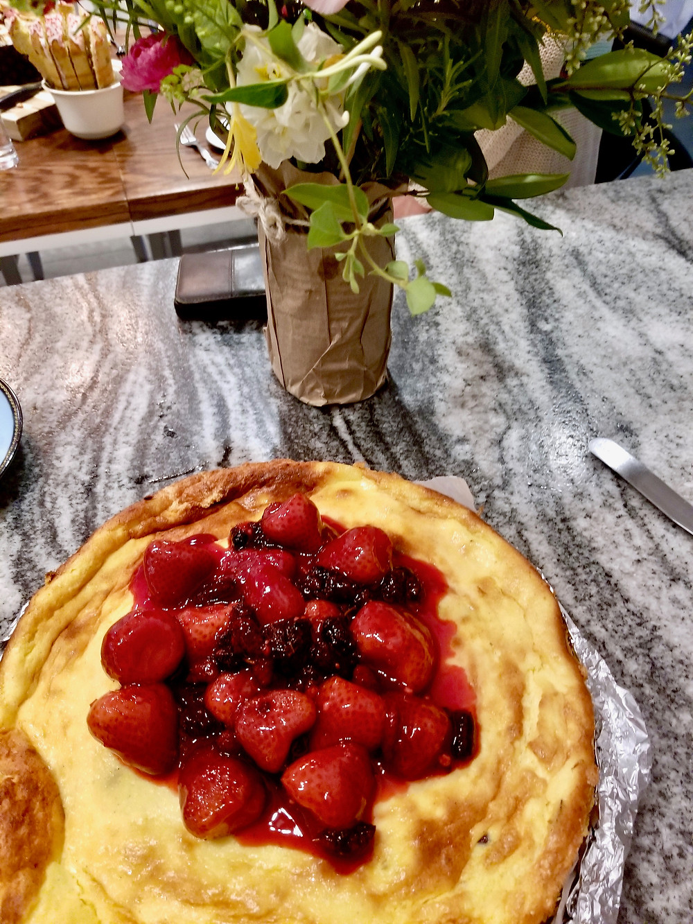 Baked farmer's cheese with berries on top on the counter with a bouquet of flowers