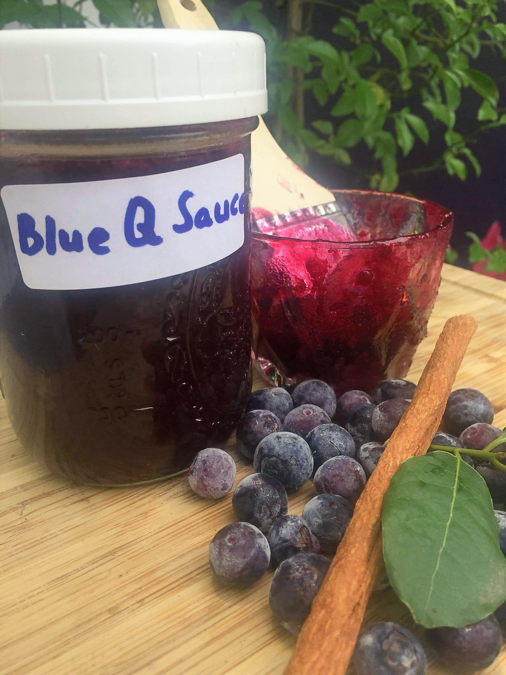 Jar of blueberry barbecue sauce with blueberries and a cinnamon stick on the side