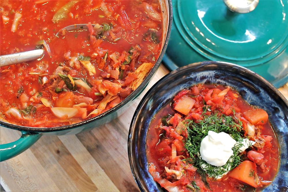 borsch in the bowl with sour cream and dill, also borsch in a pot