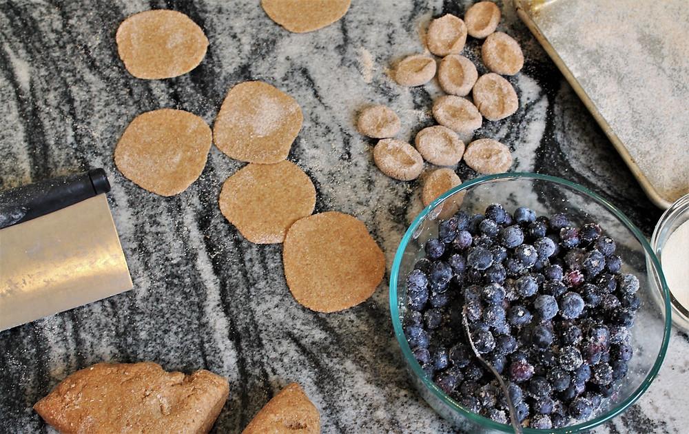 dough cutter, blueberry filling, pieces of dough, disks of dough