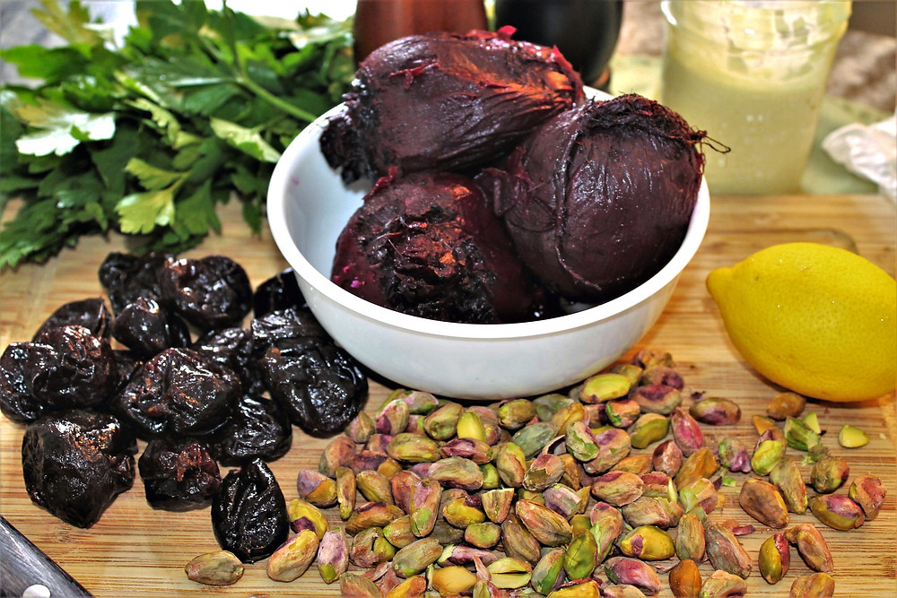 Ingredients to make a beet salad: beets, prunes, pistachios, lemons, greens, and mayonnaise